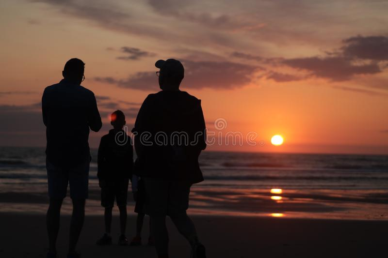 Man taking a photo of his son jumping into the sunset by the ocean sea side in France silouette. Different types of silouette people at the beach during a royalty free stock photography