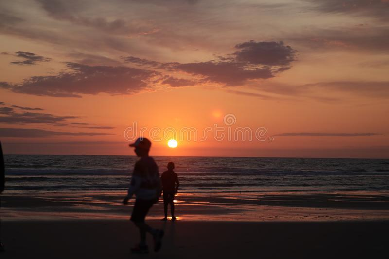 Man taking a photo of his son jumping into the sunset by the ocean sea side in France silouette. Different types of silouette people at the beach during a royalty free stock photos