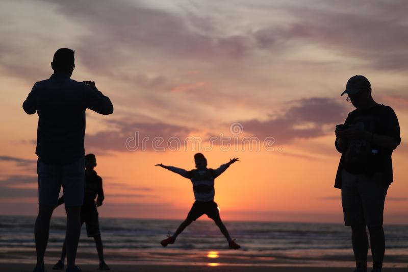 Man taking a photo of his son jumping into the sunset by the ocean sea side in France silouette. Different types of silouette people at the beach during a royalty free stock photo