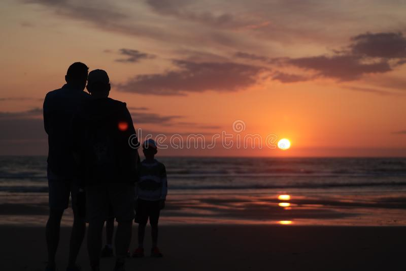 Man taking a photo of his son jumping into the sunset by the ocean sea side in France silouette. Different types of silouette people at the beach during a stock photography