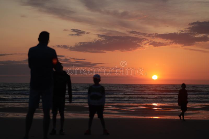Man taking a photo of his son jumping into the sunset by the ocean sea side in France silouette. Different types of silouette people at the beach during a stock photo