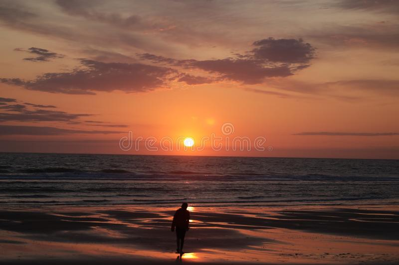 Man taking a photo of his son jumping into the sunset by the ocean sea side in France silouette. Different types of silouette people at the beach during a stock images