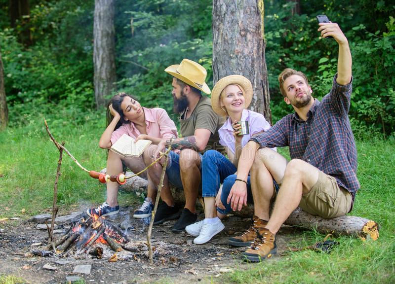 Man taking photo near bonfire nature background. Tourists sit log near bonfire taking selfie photo smartphone. Friends. On vacation capture moment. Friends near stock image