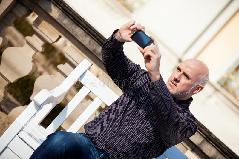 Man taking a photograph with his mobile. Attractive bald middle-aged man sitting on a wooden bench in an urban setting taking a photograph with his mobile phone stock photography
