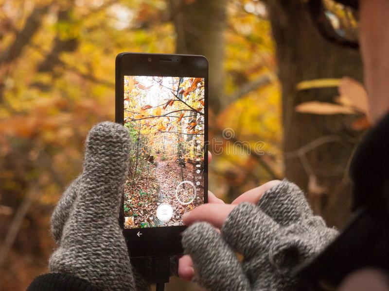 Man taking a picture with camera smart phone touch screen nature stock image