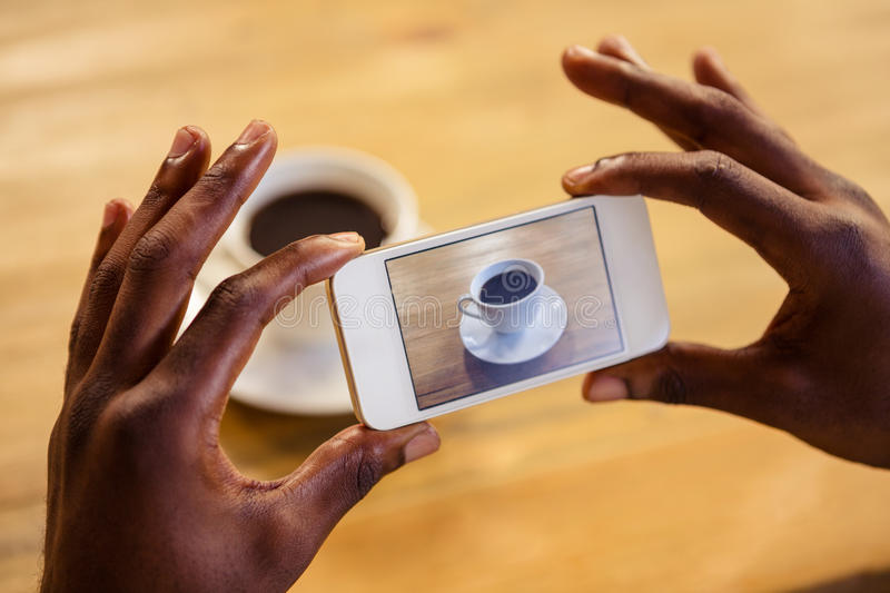 Man taking picture of a coffee. In the cafe royalty free stock photography