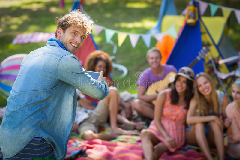Man taking a picture of friends at campsite. Portrait of man taking a picture of friends at campsite on a sunny day royalty free stock image