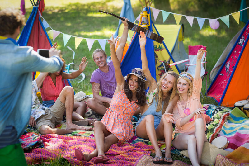 Man taking a picture of friends at campsite. On a sunny day royalty free stock photo
