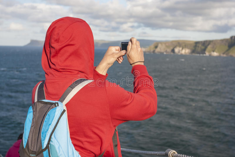Man taking a picture. Middle age man taking a picture of the cliff at Carrick a rede in North Antrim, Northern Ireland royalty free stock photo