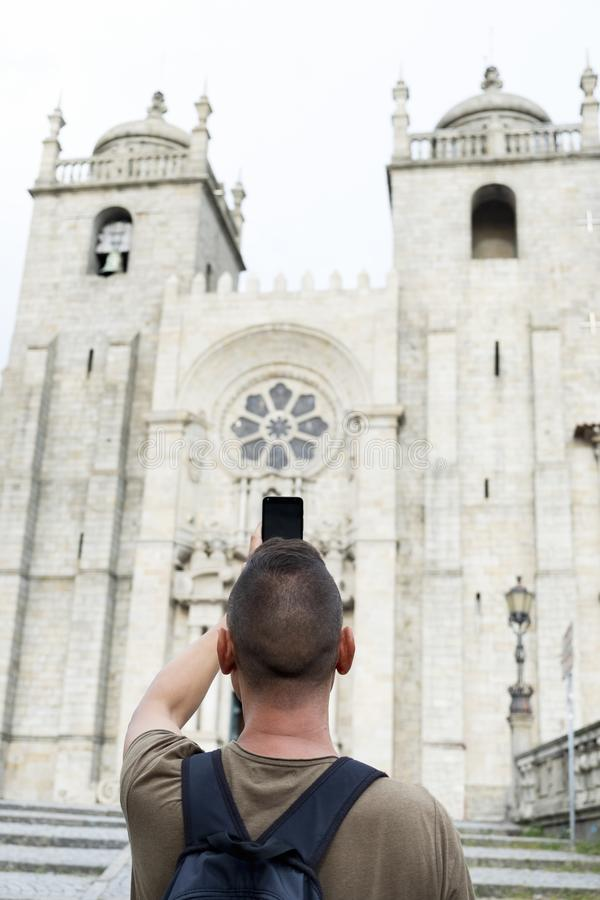 Man taking a picture of Porto Cathedral, Portugal royalty free stock photo