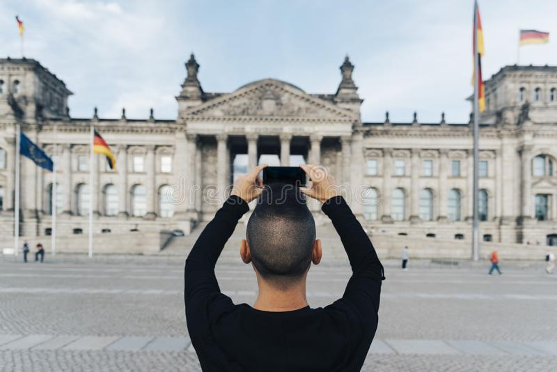 Man taking a picture of the Reichstag, in Berlin. Closeup of a young caucasian man, seen from behind, taking a picture of the facade of the Reichstag building in royalty free stock image