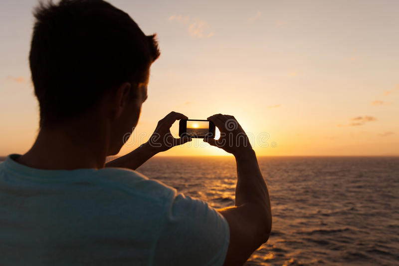 Man taking picture sunset. Man taking picture of beautiful sunset over sea stock photos