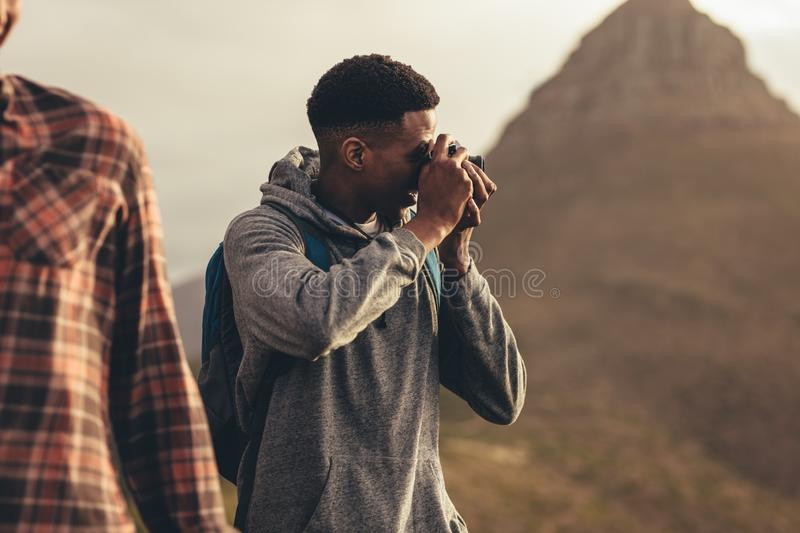 Man taking pictures during a hike with friends. Social media influencer capturing new content of this social media during a hike stock photography