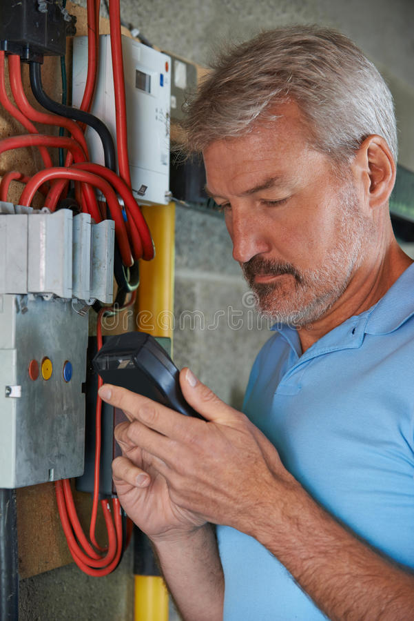 Man Taking Reading From Electricity Meter stock photography