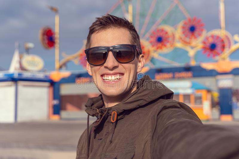 Man taking a selfie in coney island. Luna park as background royalty free stock image