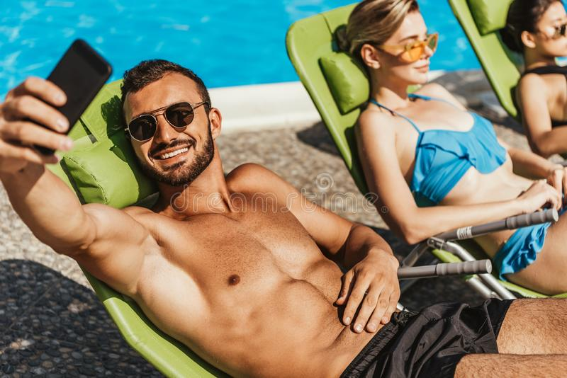 Man taking selfie with girls sunbathing on sunbeds. At poolside royalty free stock images