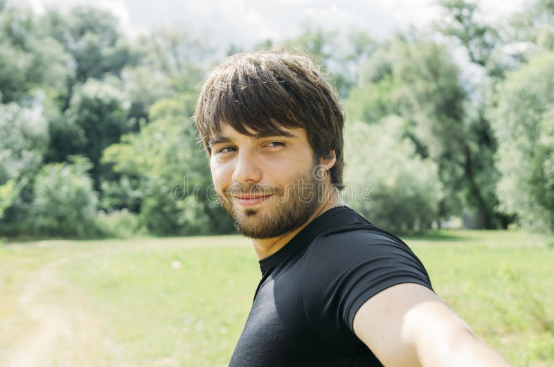 Man taking selfie. Portrait of young handsome man holding camera and taking outdoor selfie with smartphone. Guy enjoy nature, smiling and looking back in camera stock images