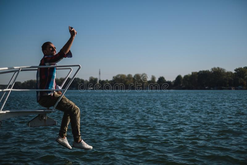 Man taking selfie while sitting on the river boat royalty free stock photography