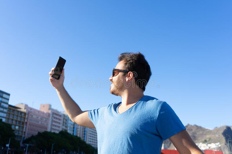 Man taking a selfie in urban area and smiling. 30s guy with positive and confident attitude making and sharing a story in social stock image