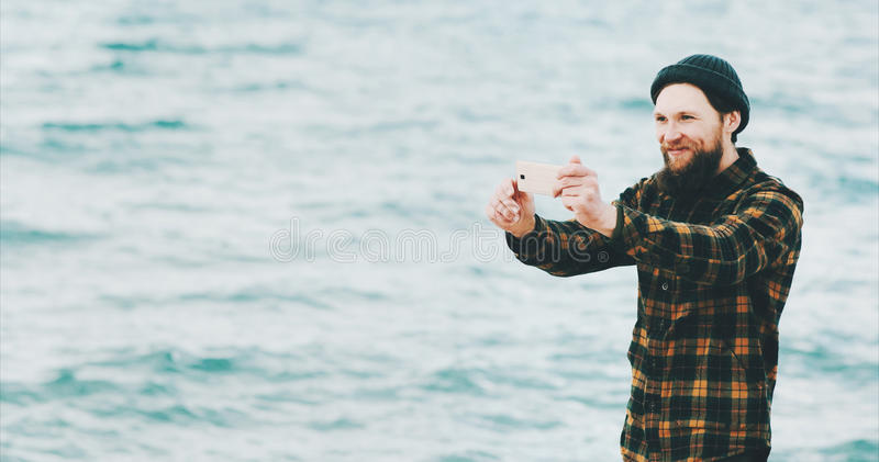 Man taking selfie using Smartphone and talking online. At sea Travel Fashion Lifestyle and modern technology concept happy emotions summer vacations stock photos
