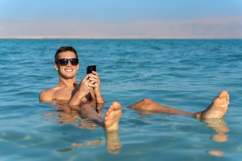 Young man floating on the water surface of the dead sea and using his smartphone stock photography
