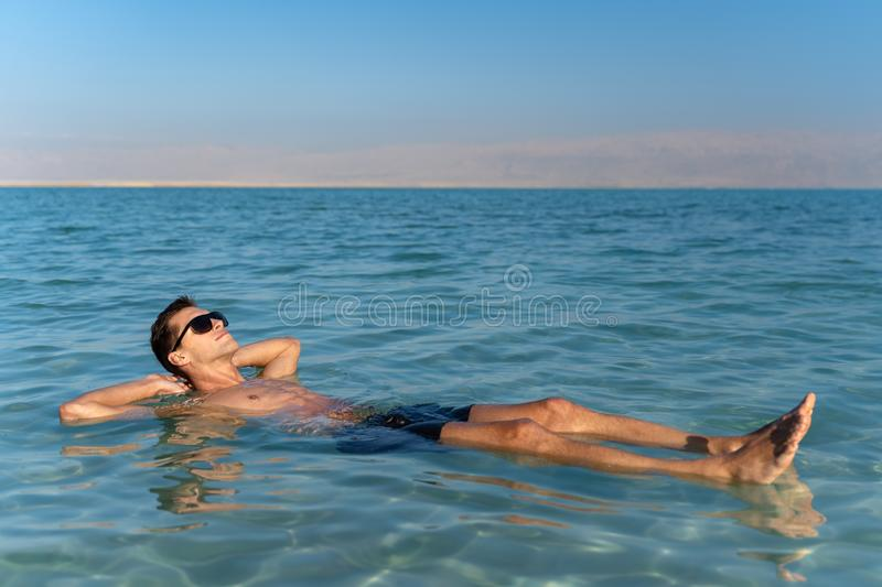 Young man floating on the water surface of the dead sea stock photo