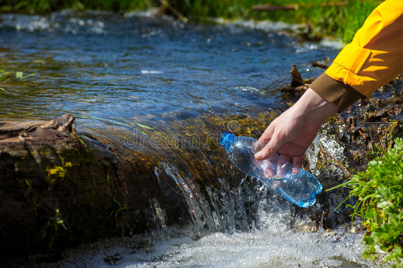 Man taking water from forest on hiking trip02 royalty free stock image