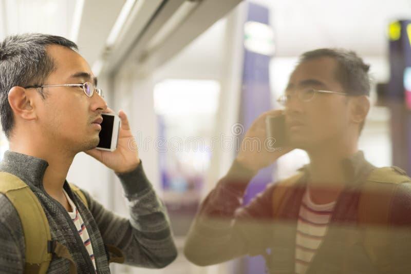 Man talk phone. Man talk on phone in Hong Kong subway, asian stock image
