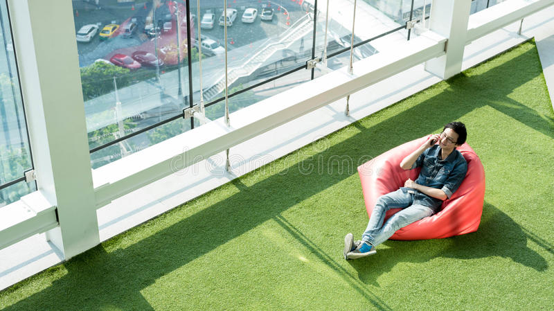 Man talk via smartphone on bean bag in afternoon, freelance conceptual lifestyle, internet in everyday life stock photos
