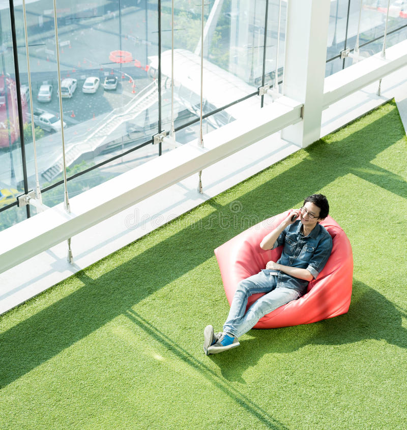 Man talk via smartphone on bean bag in afternoon, freelance conceptual lifestyle, internet in everyday life royalty free stock images