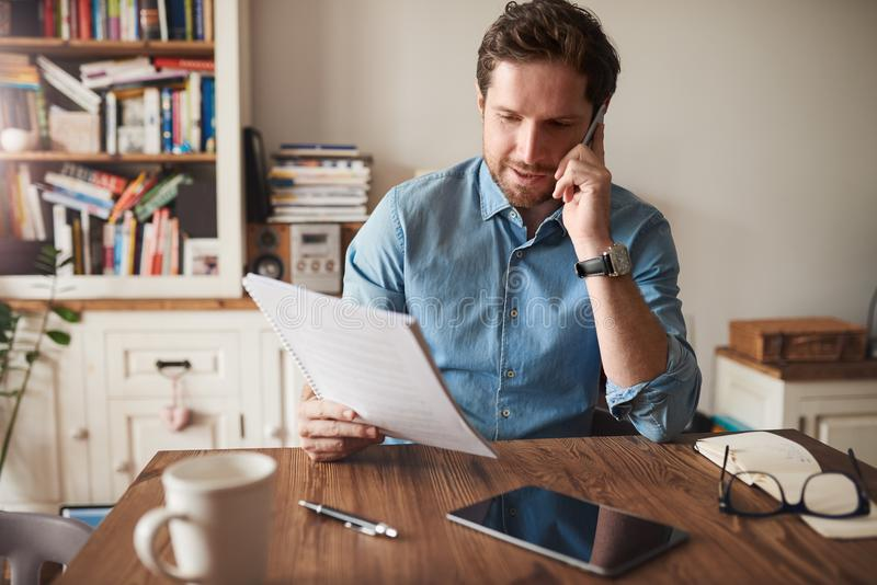 Man talking on a cellphone while reading paperwork at home royalty free stock photos