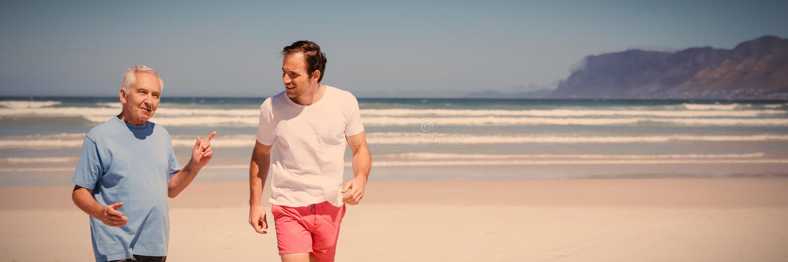 Man talking with his father while walking at beach royalty free stock photos