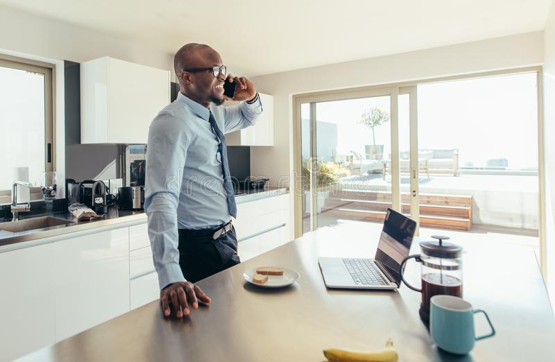 Man talking over phone while having breakfast. Businessman talking over mobile phone while having breakfast. Man talking on phone with laptop computer and stock photo