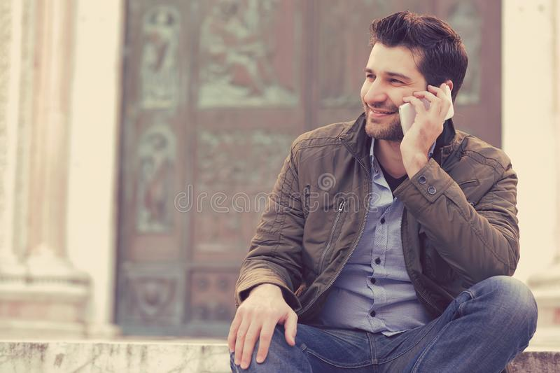 Man talking on a phone. Casual professional using smartphone smiling outside old building. stock image