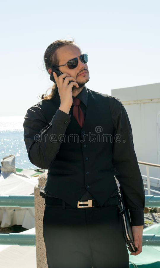 Man talking on the phone by the sea shore stock image