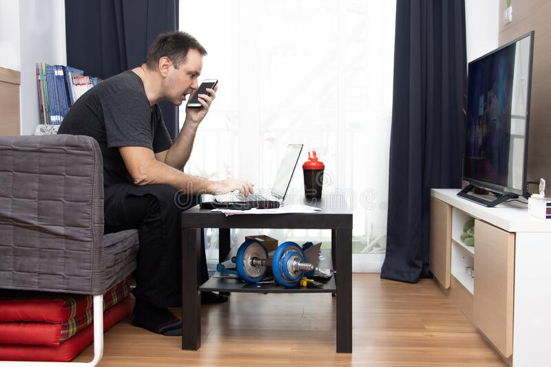 A man talking on the phone while sitting in living room with TV and laptop stock photos