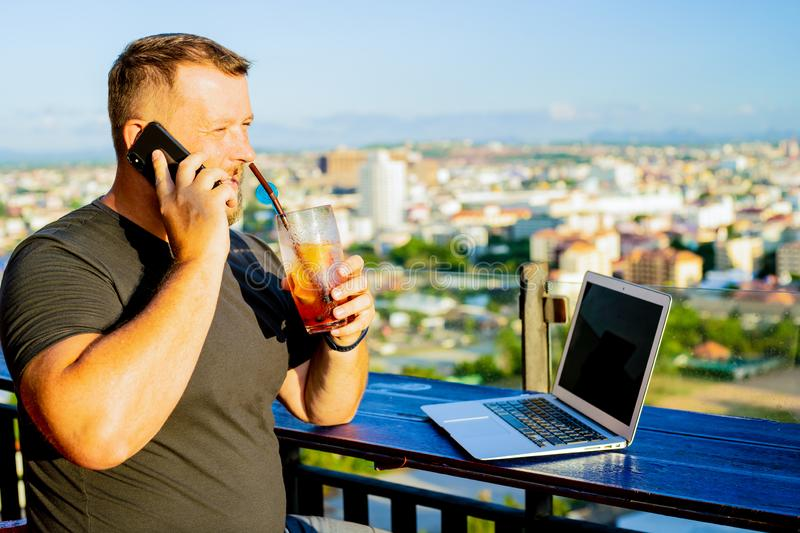 Man talking on the phone and working on a computer in a cafe with a beautiful view royalty free stock image