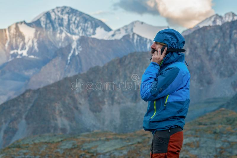 Man talking on a satellite phone in the mountains.  stock photos