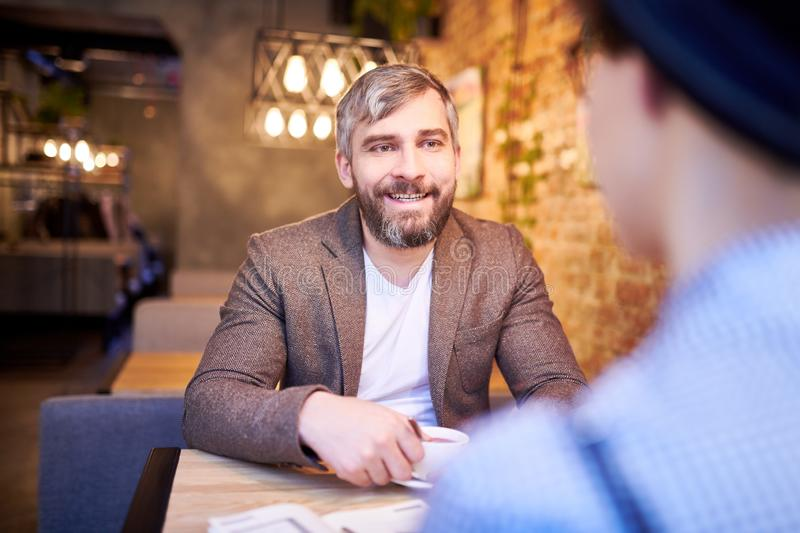 Man talking to colleague. Happy bearded men having tea or coffee in cafe and discussing working points with colleague royalty free stock image
