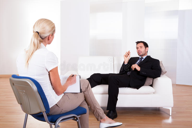 Man talking to his psychiatrist. Over the shoulder view of a business men reclining comfortably on a couch talking to his psychiatrist explaining something stock image