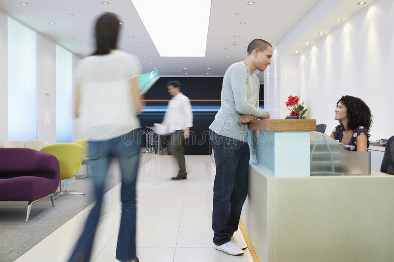Man Talking To Receptionist At Office. Man talking to receptionist at the reception desk in office stock photography