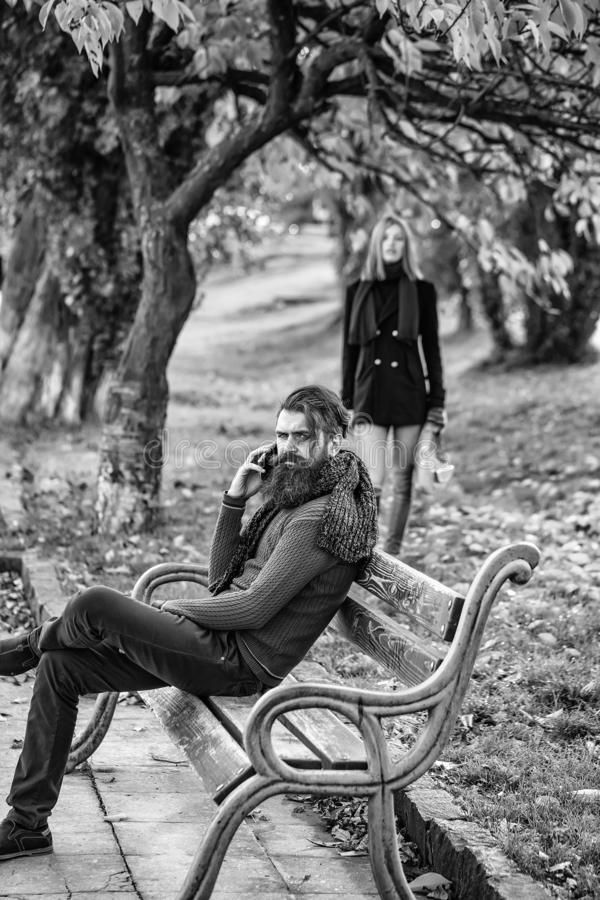 Man talks on phone. Bearded men hipster talks on phone on bench with pretty girl outdoors in autumn park with yellow leaves on natural background stock photos
