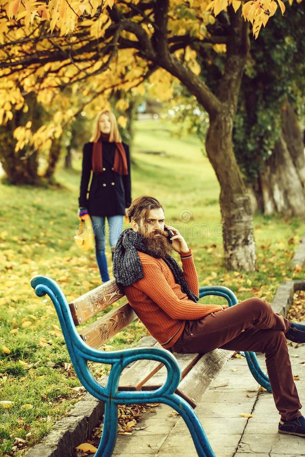 Man talks on phone. Bearded men hipster talks on phone on bench with pretty girl outdoors in autumn park with yellow leaves on natural background royalty free stock image