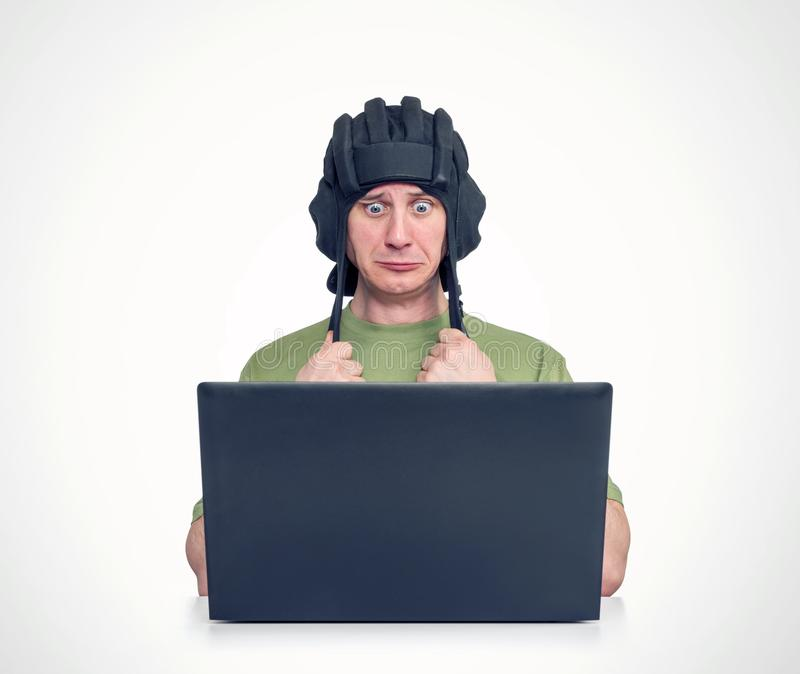 Man in tank helmet playing in game, sitting front of laptop. Concept of losing stock photography