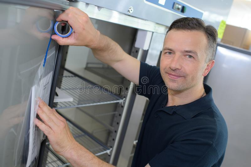 Man taping instructions to door refrigerator stock image