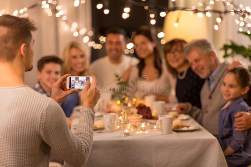 Man tar en bild av familjen på middagsfesten arkivfoto