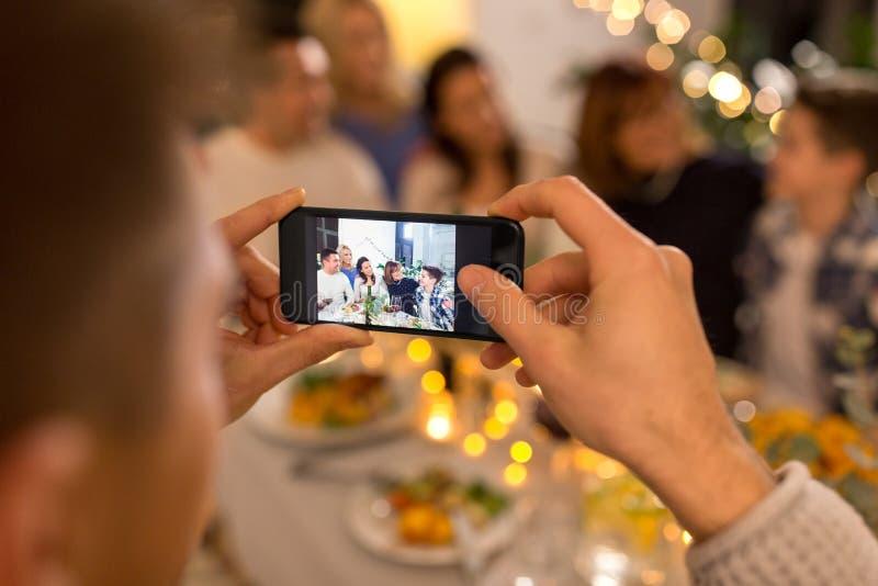 Man tar en bild av familjen på middagsfesten arkivfoton