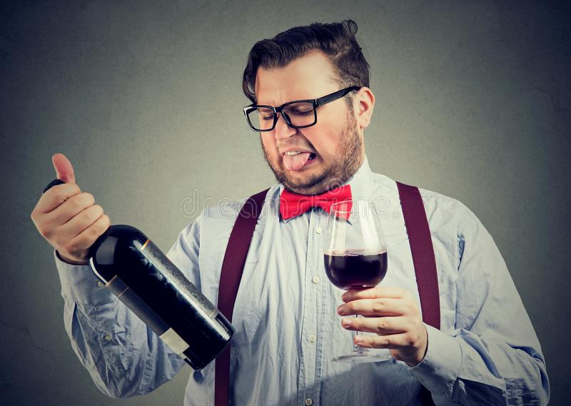 Man tasting wine and looking at bottle stock photography
