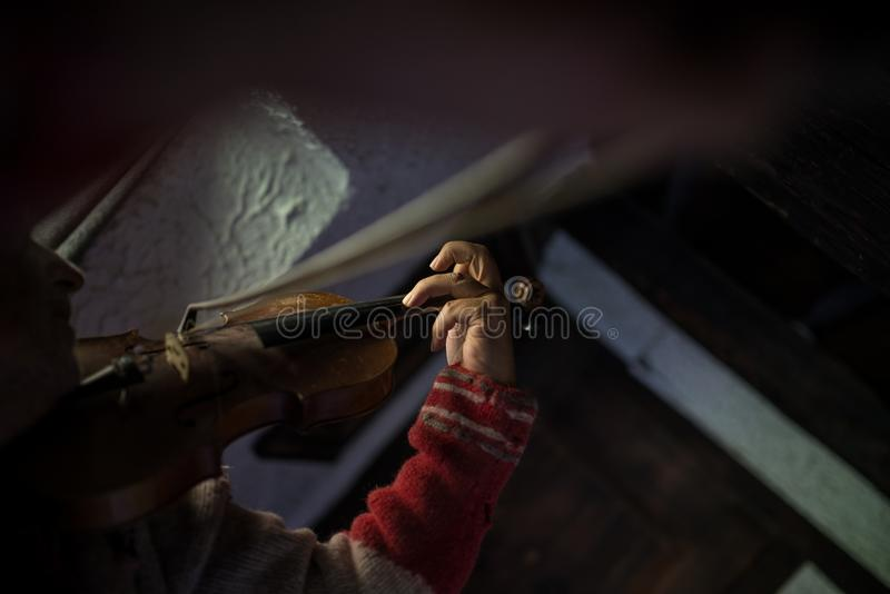 Man in a tattered old torn jersey playing a violin in a darkened royalty free stock images