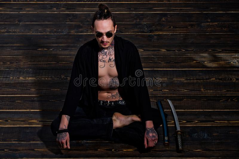 Man with tattooed torso sitting in meditation pose with swords stock photography